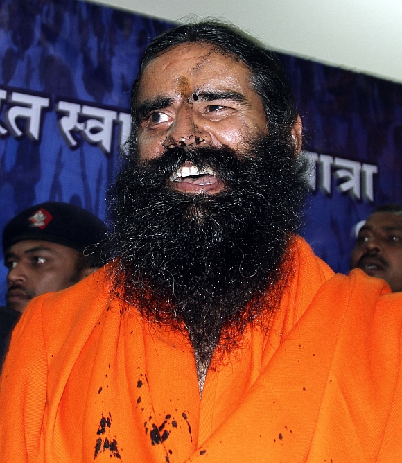 Ramdev reacts with his face smeared with black ink after addressing a news conference in New Delhi