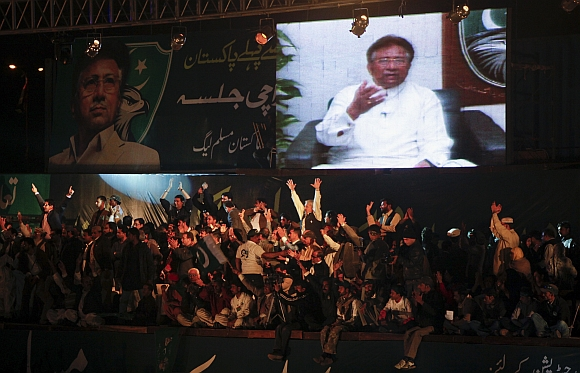 Leaders and supporters of the political party All Pakistan Muslim League surround a screen broadcasting a speech by their party president Pervez Musharraf from Dubai via video link, in Karachi