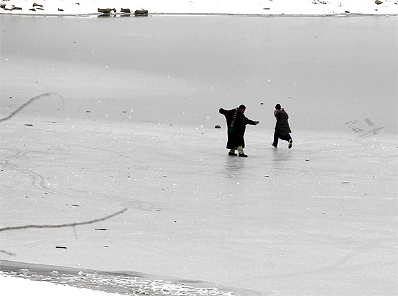 Kashmiri boys play on the semi-frozen layer of a water reservoir on a cold day on the outskirts of Srinagar