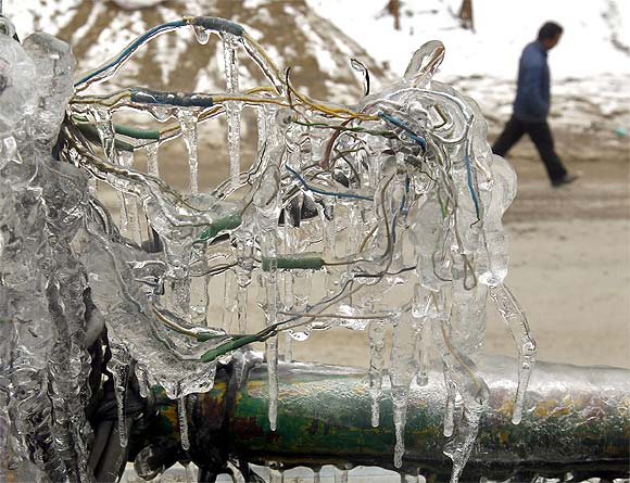 Wires frozen with ice are seen from the first floor of a building as a Kashmiri man walks on a road below in Srinagar