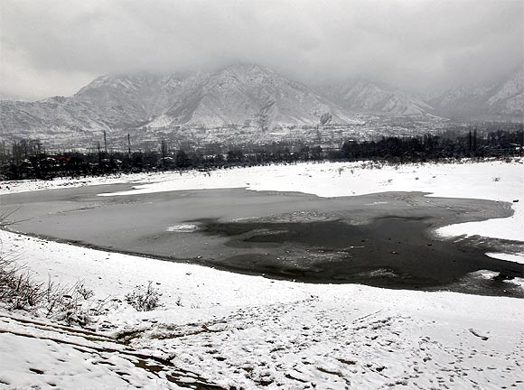 A view shows the semi-frozen layer of a water reservoir on a cold day on the outskirts of Srinagar