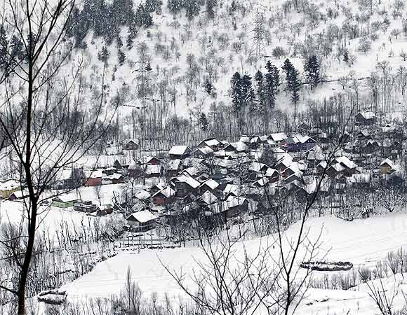 A view of snow-covered houses seen from Srinagar-Jammu highway