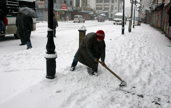 A boy clears snow from the pavement