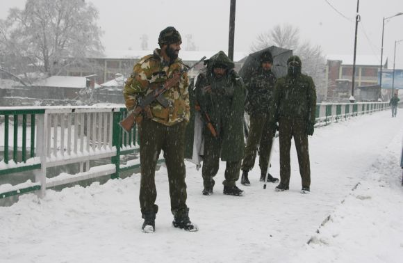 Security personnel keep watch as it snows in Srinagar