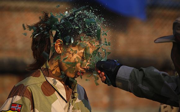 An instructor from the Tianjiao Special Guard/Security Consultant Ltd. Co, smashes a bottle over a female recruit's head during a training session for China's first female bodyguards in Beijing