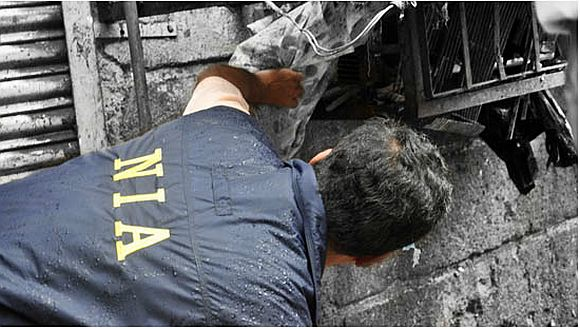 A NIA officer investigating the site of a bomb blast in Mumbai