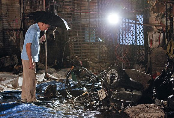A plain-clothed policeman surveys the aftermath at the site of an explosion near the Opera House in Mumbai in July, 2011