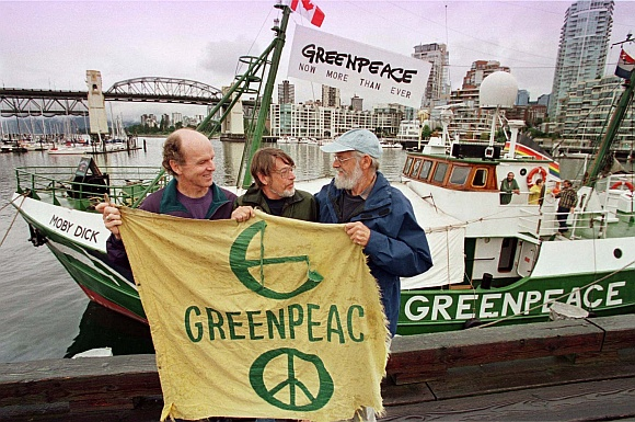 Three founding members of Greenpeace Bill Darnell (L), Lyle Thurston (C) and Jim Bohlen (R) hold the original banner as they stand in front of one of the group's current vessels, the 'Moby Dick' during celebrations of Greenpeace's 25th anniversary in Vancouver