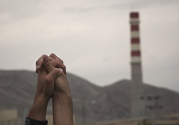 Iranian students hold up their hands as a sign of unity as they form a human chain around the Uranium Conversion Facility to show their support for Iran's nuclear program in Isfahan