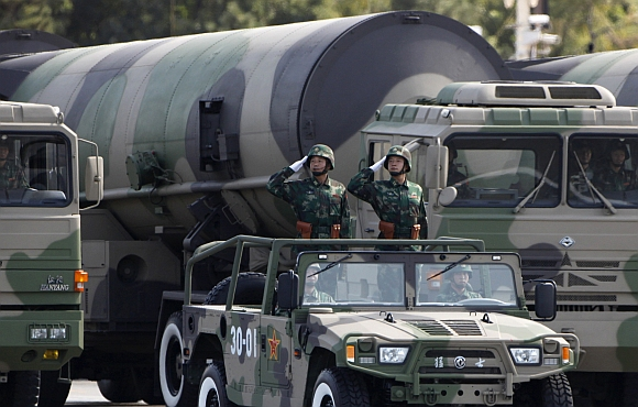 People's Liberation Army soldiers salute in front of nuclear-capable missiles during a massive parade to mark the 60th anniversary of the founding of the People's Republic of China in Beijing