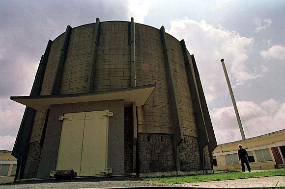 A worker is dwarfed by a rusting United States-built Buck Rogers-style reactor at Vietnam's Atomic Research Centre, containing the deadly plutonium left by the U S in March 1975 following the end of the war