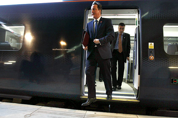 Britain's Prime Minister David Cameron exits a train at Stratford station to attend a cabinet meeting at the 2012 Olympic Games site in London