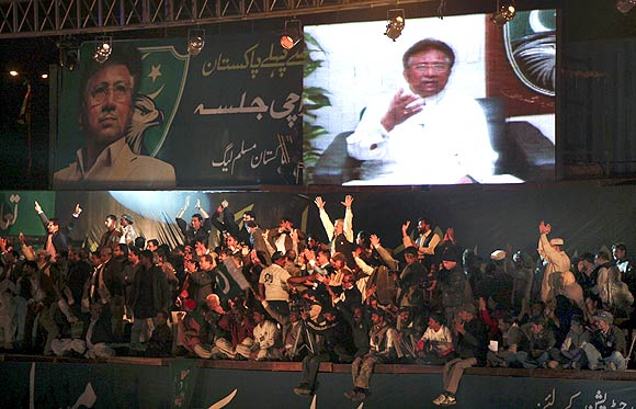 All Pakistan Muslim League supporters watch a screen broadcasting a speech by their party president Pervez Musharraf
