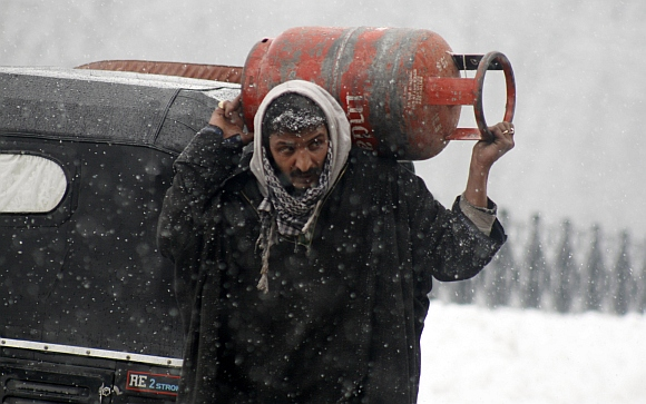 A man walks with a gas cylinder in heavy snow