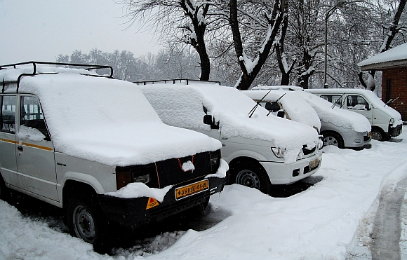 Vehicles covered under a sheet of snow at a parking lot