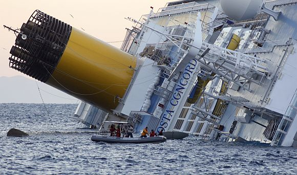 Rescuers stand in a boat next to the Costa Concordia cruise ship