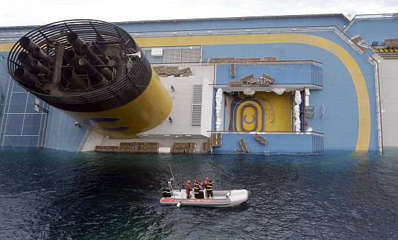 Rescuers stand in a boat next to the Costa Concordia