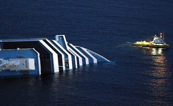 Rescue workers inspect the side of the Costa Concordia