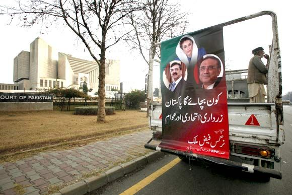 A banner bearing images of Pakistan's PM Gilani, former PM Bhutto and President Zardari outside the Supreme Court building in Islamabad. Gilani has been asked by the apex court to appear before it on Saturday.