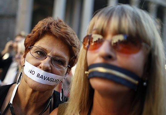 Women, who put a zip and a tape on their mouths, protest against a privacy law in downtown Rome