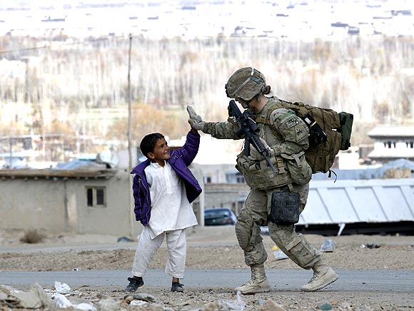 A US Army soldier with a local boy during a patrol in Pul-e Alam, a town in Logar province, Afghanistan.
