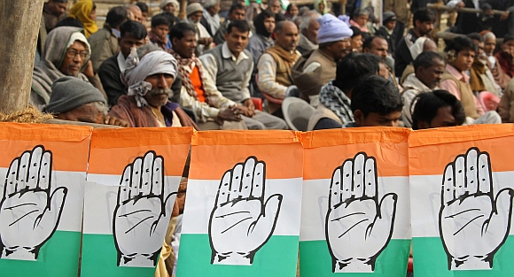 Congress supporters sit next flags of party's logo as they attend an election campaign rally