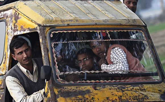 People travel in a motorised rickshaw on a street in Rae Bareli