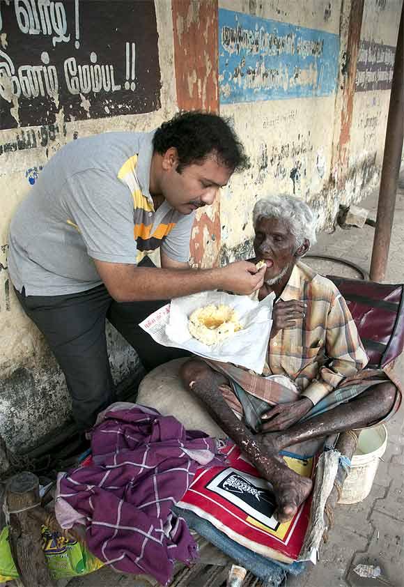 Narayanan Krishnan feeds a mentally ill man in Madurai