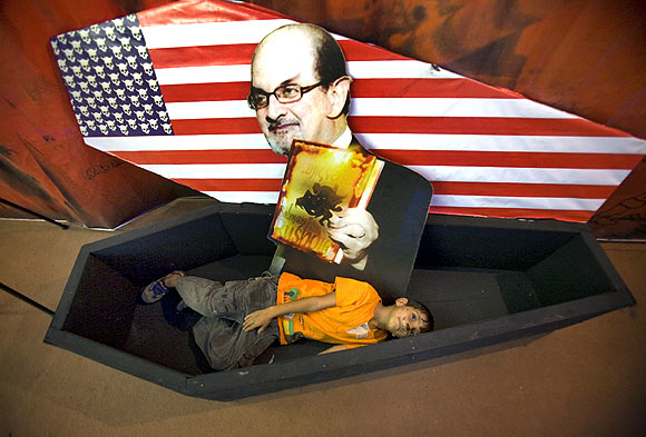 A boy lies in a symbolic coffin for with a picture of author Salman Rushdie
