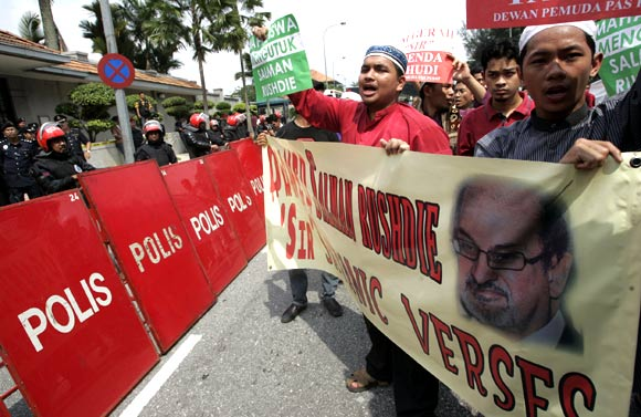 Protesters hold placards and shout slogans during a demonstration against Salman Rushdie