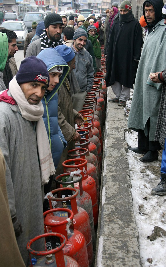 People wait in long queues to collect LPG cylinders.