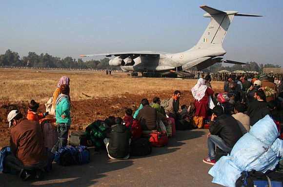 Stranded passengers waiting to aboard a special aircraft of the IAF at the airport in Jammu, on Saturday