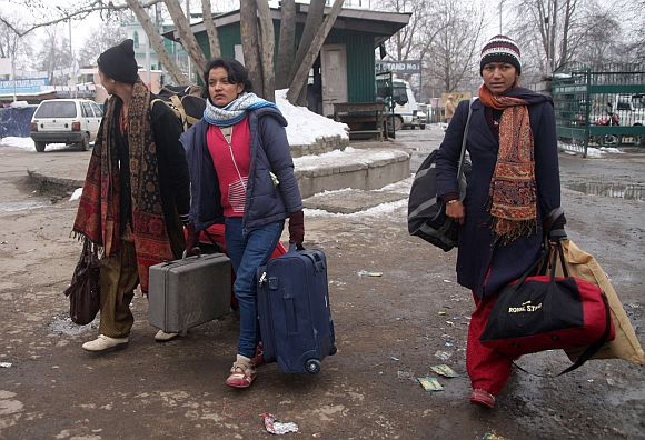 Stranded tourists walk to board the special IAF aircraft, in Srinagar, on Saturday
