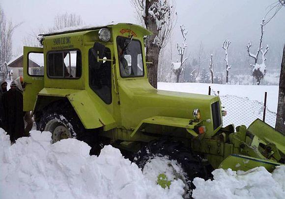 Beacon workers clear a snow-clogged Jammu Srinagar highway on Saturday