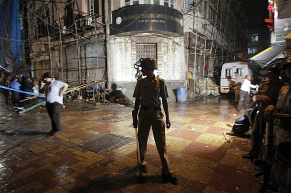 A policeman stands guard at the site of an explosion in the Zaveri Bazar