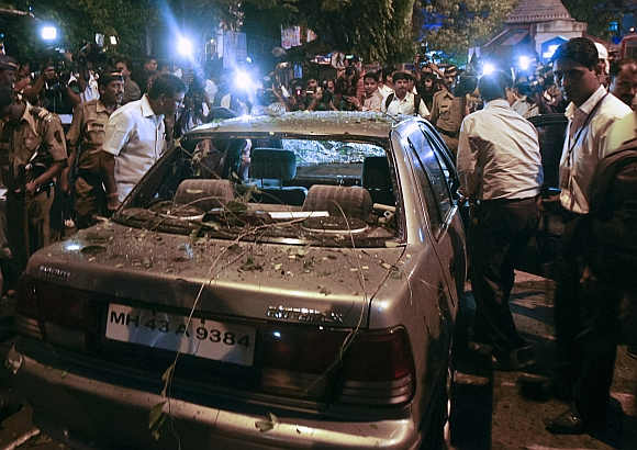 Policemen surround a vehicle which was damaged at the site of an explosion in the Dadar area on July 13. 2011