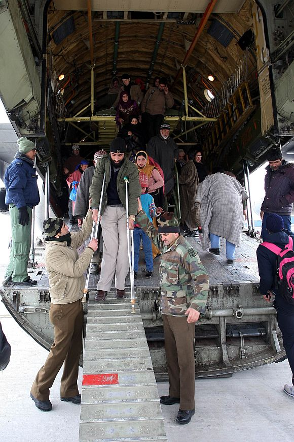 Defence personnel help a handicapped civilian disembark at Jammu air base