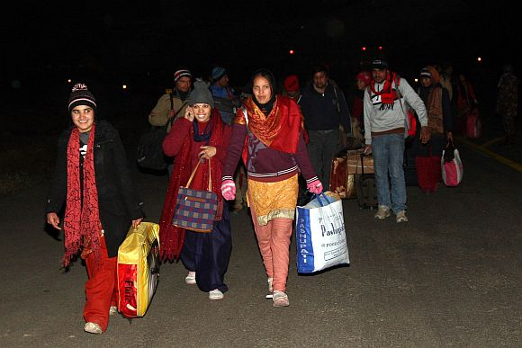 All smiles: Rescued tourists exit the runway at the Jammu air base