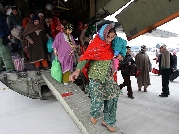 Rescued civilians disembark on arrival at the Jammu air base