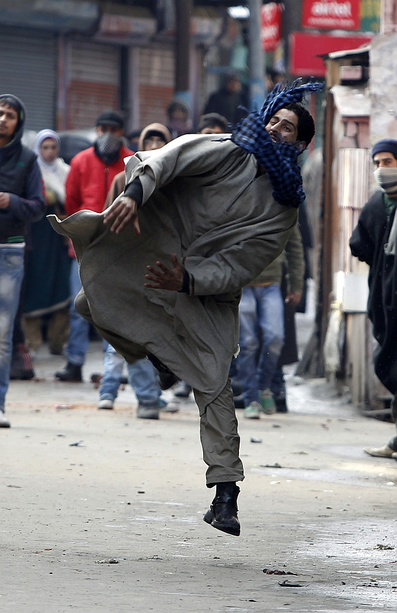 A Kashmiri protester throws stones toward Indian police during a protest in Srinagar