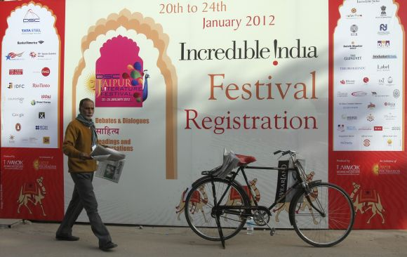 A newspaper vendor walks past an advertisement hoarding outside the venue of the annual Literature Festival in Jaipur