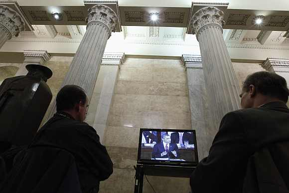Journalists watch a television broadcast of Obama's speech