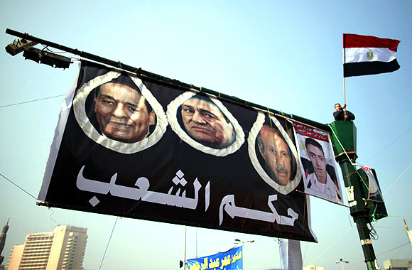 A demonstrator waves an Egyptian flag next a poster of former President Hosni Mubarak (C) and Field Marshal Mohamed Hussein Tantawi (L) during a protest marking the first anniversary of Egypt's uprising at Tahrir square