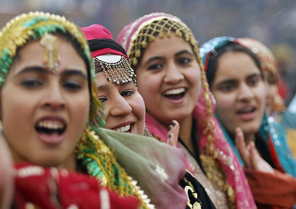Kashmiri schoolgirls wearing traditional dresses perform to a patriotic song