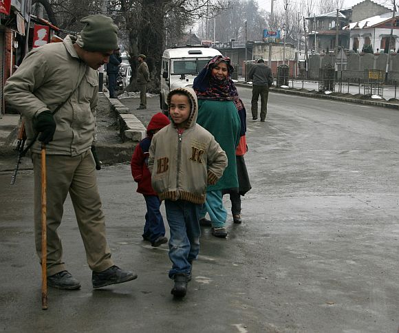 A policeman shares a light moment with a Kashmiri boy