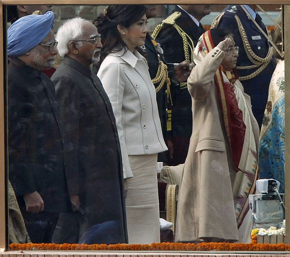 (From L - R) Prime Minister Manmohan Singh, Vice President Mohammad Hamid Ansari, Thailand's Prime Minister Yingluck Shinawatra and President Pratibha Patil stand behind a bullet-proof glass during India's national anthem at the Republic Day parade