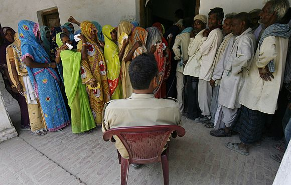 Voters wait to cast their votes in Rohania, UP