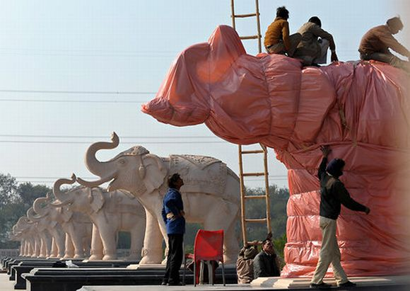 Election Commission-appointed workers cover the statues of elephants, which also happen to be the ruling Bahujan Samaj Party's election symbol, in Lucknow