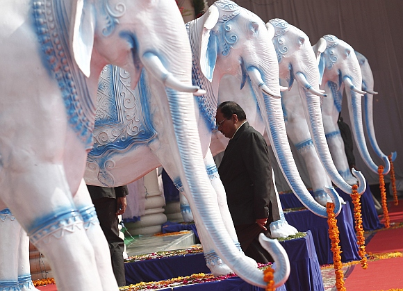 A Bahujan Samaj Party worker walks past statues of elephants, the BSP's electoral symbol, at the party headquarters in Lucknow