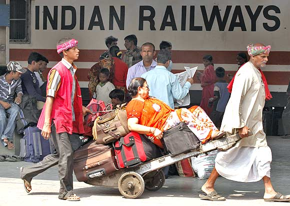 Porters transport a passenger and her luggage in Kolkata